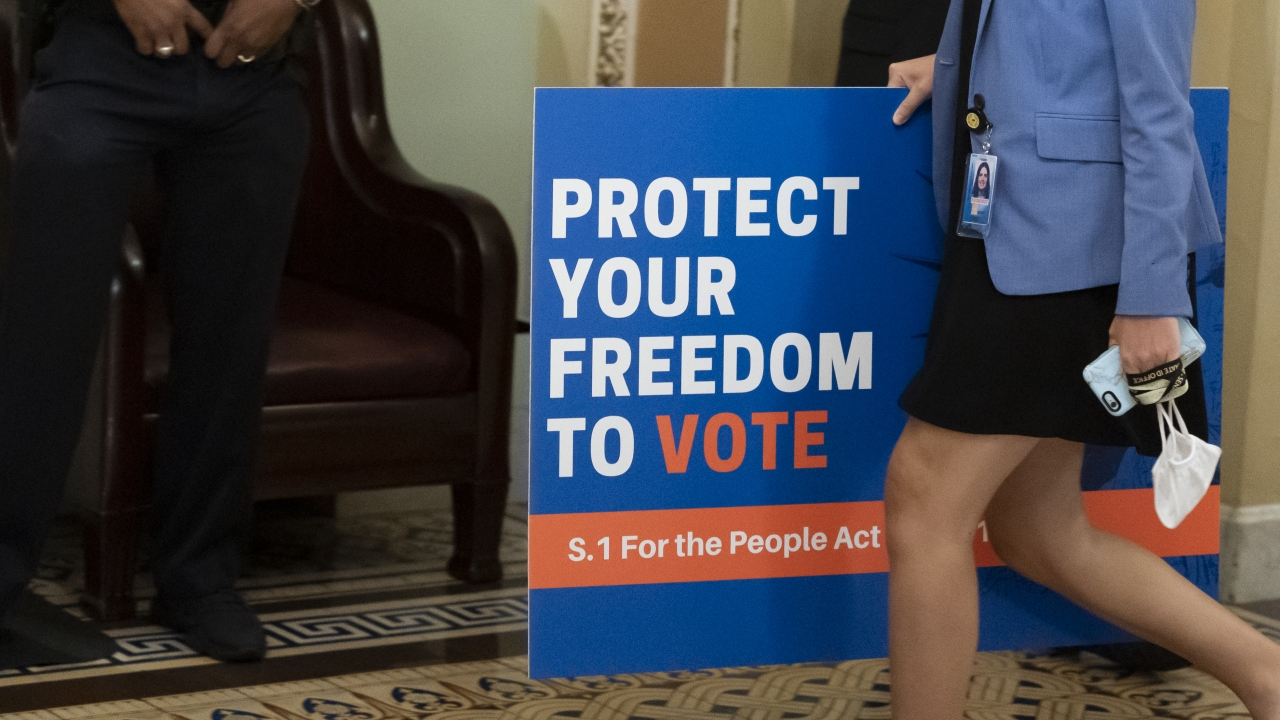 An aide carries a sign to the Senate floor as the Senate prepares for a key test vote on the For the People Act