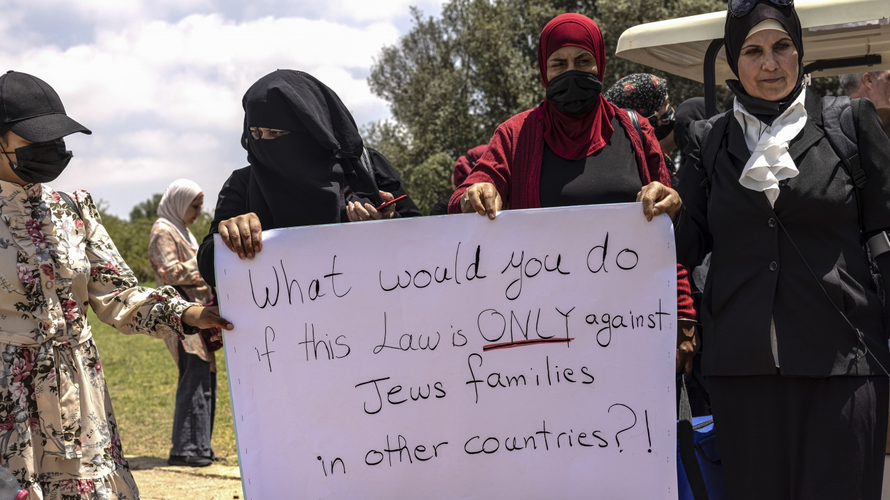 Israeli Arab women hold a sign during a protest ahead of a vote by Israel's parliament.