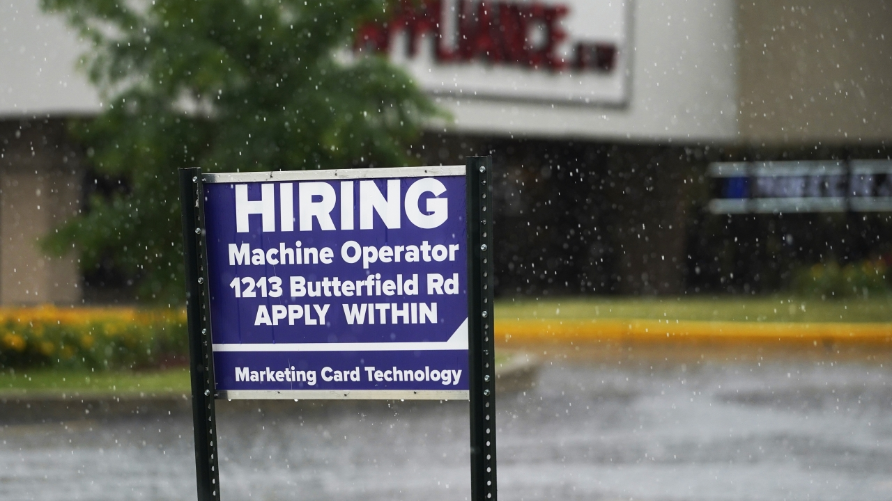 A hiring sign is displayed in Downers Grove, Ill.