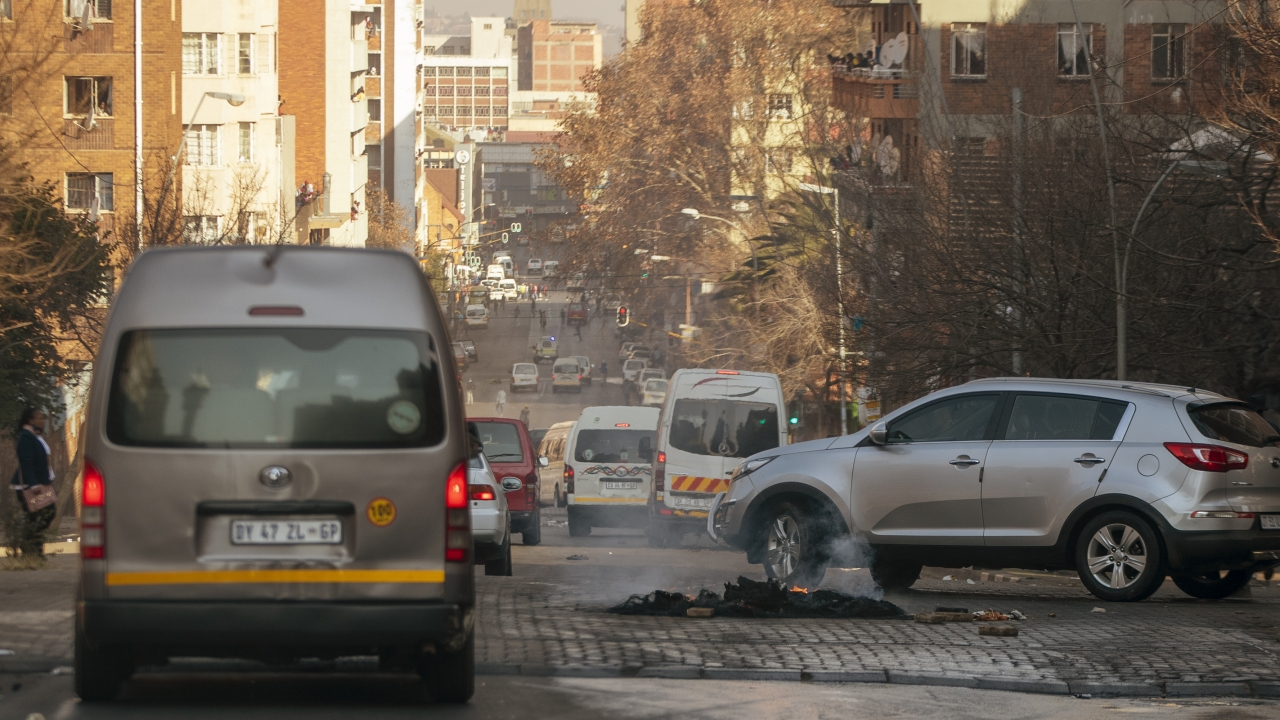 Cars drive around a burning tire on the street in Hillbrow, Johannesburg, South Africa