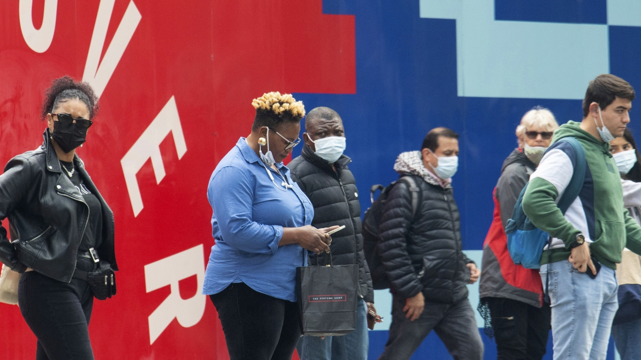 People wearing face masks to protect against coronavirus, walk, in central London