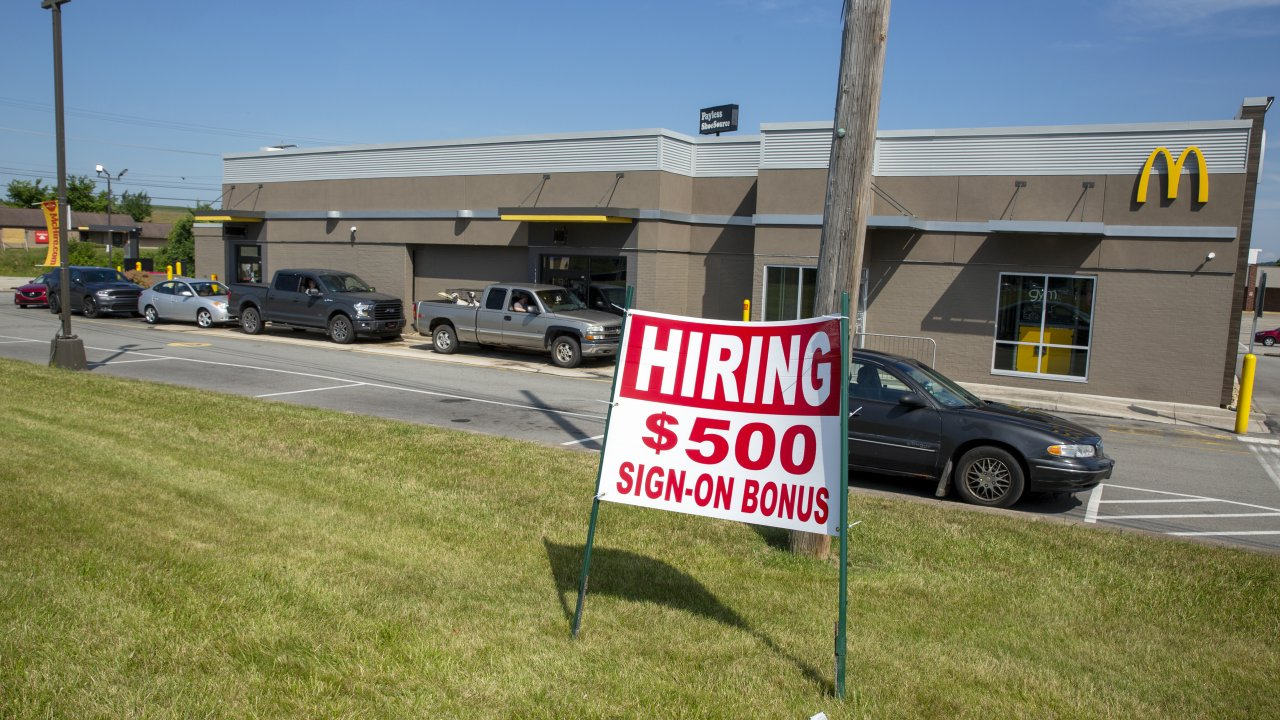 A hiring sign offering a $500 bonus is posted in front of a McDonald's.