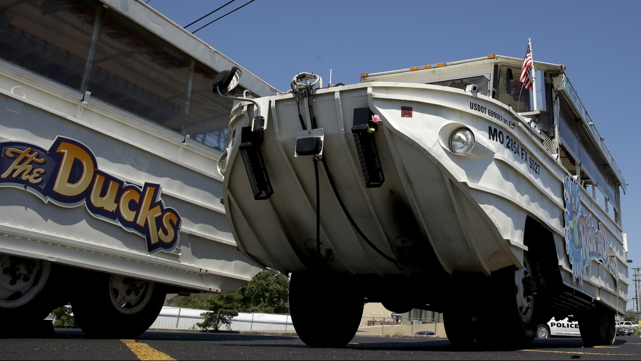 A man looks at an idled duck boat in the parking lot of Ride the Ducks
