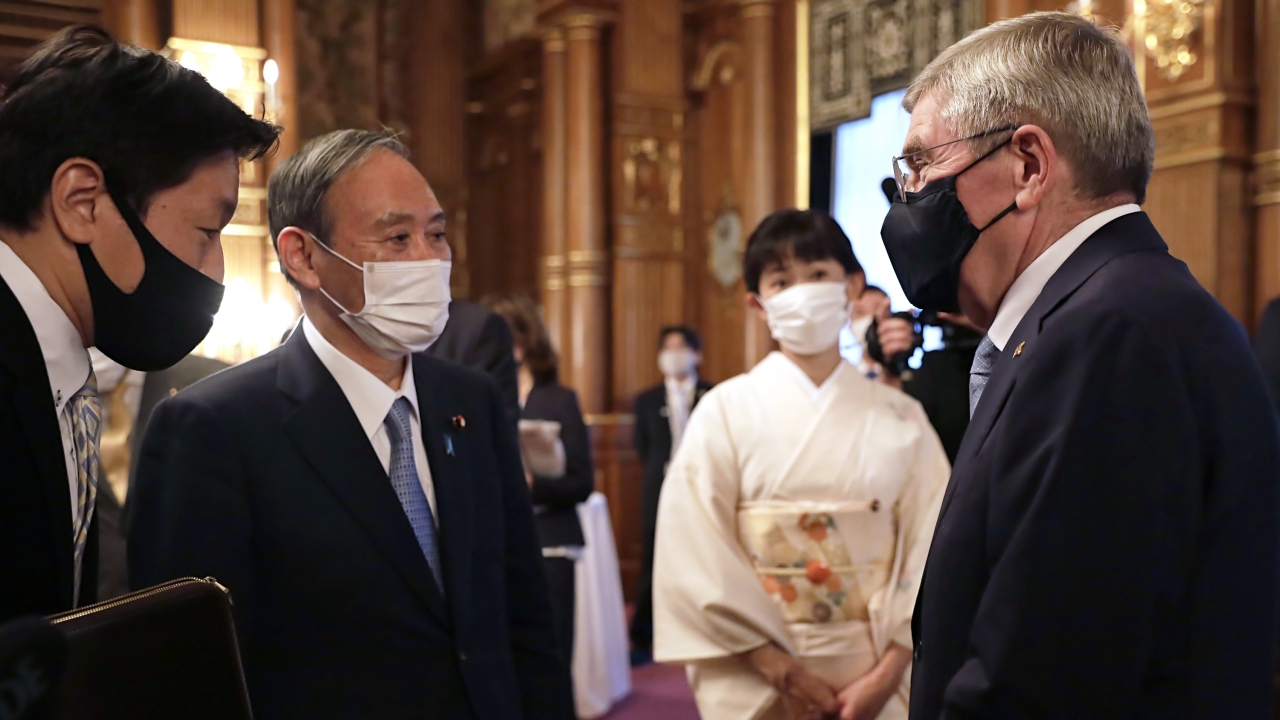 IOC President Thomas Bach, right, meets with Japanese Prime Minister Yoshihide Suga,