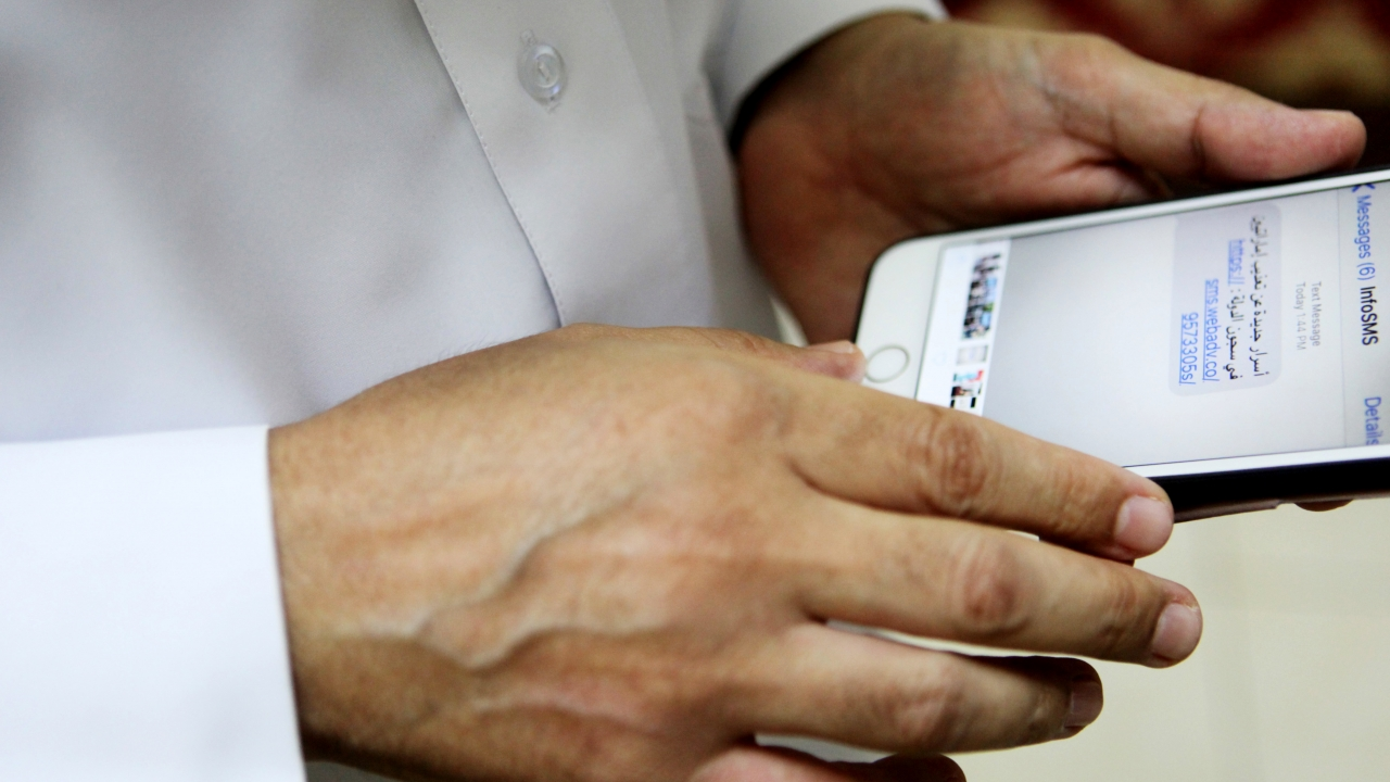 Human rights activist Ahmed Mansoor shows screenshot of spoof text message.