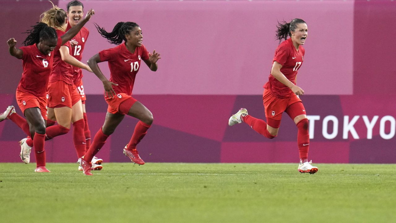 Canada's Jessie Fleming, right, celebrates scoring the opening goal from the penalty spot during a women's semifinal match.