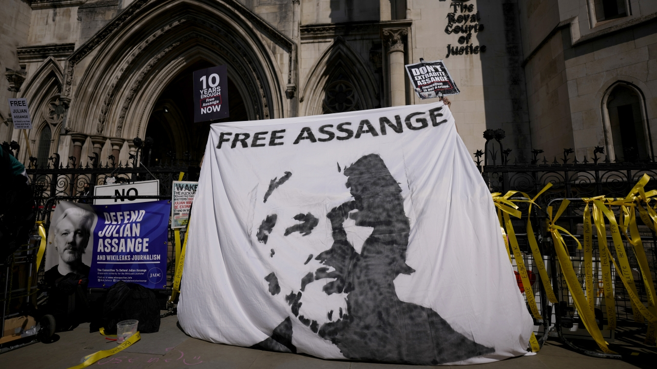 Supporters of WikiLeaks founder Julian Assange hold up a banner as they protest, during the first hearing in the Julian Assan