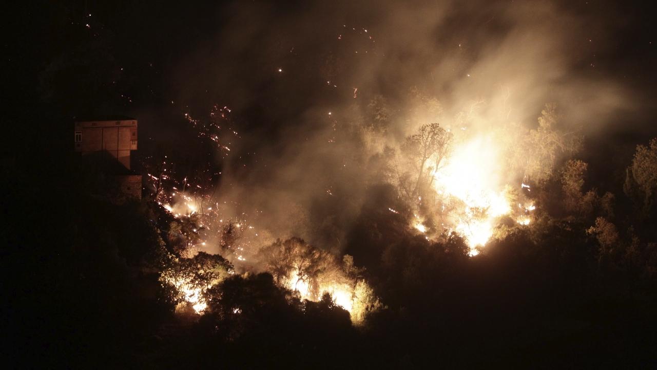 A forest burns near the village of Larbaa Nath Irathen, neat Tizi Ouzou, in the mountainous Kabyle region