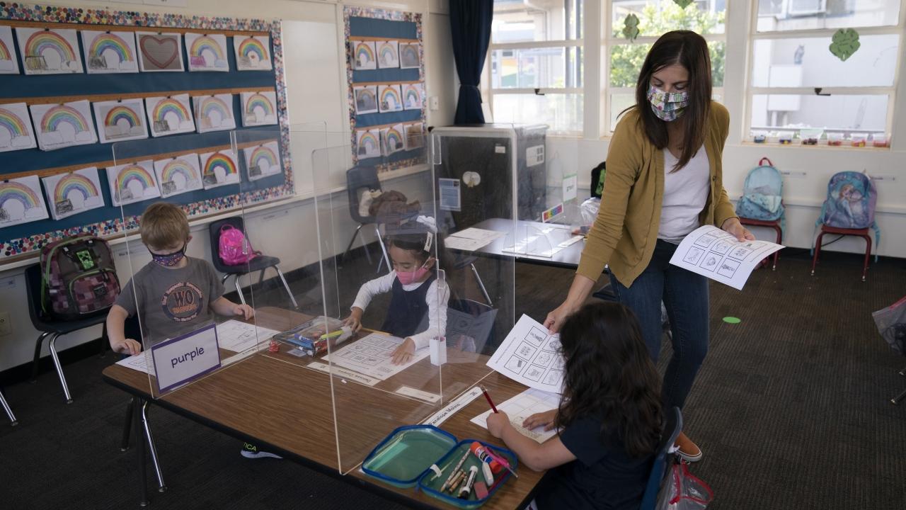 Kindergarten teacher hands printouts to her students at West Orange Elementary School in Orange, California