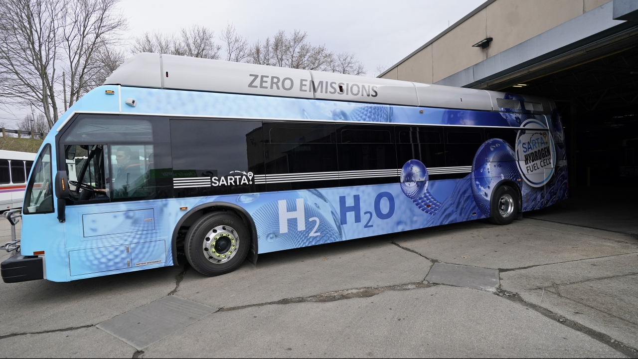 A maintenance technician, drives a hydrogen fuel cell bus out of the terminal