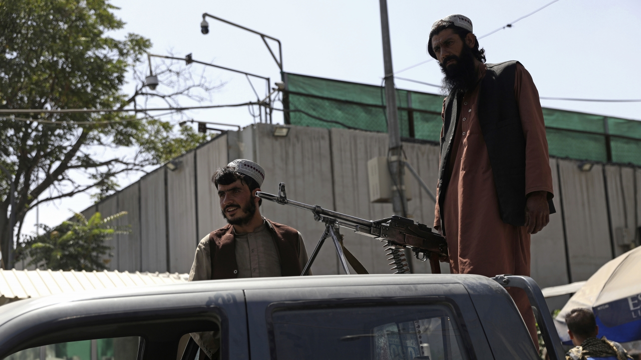 Taliban fighters stand guard on the back of vehicle with a machine gun near the Afghan presidential palace.