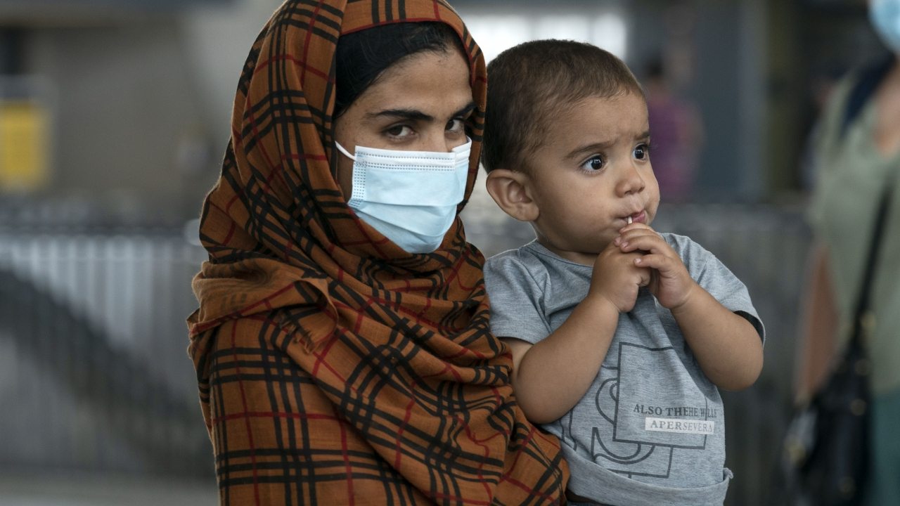 Families evacuated from Kabul, Afghanistan, walk through the terminal