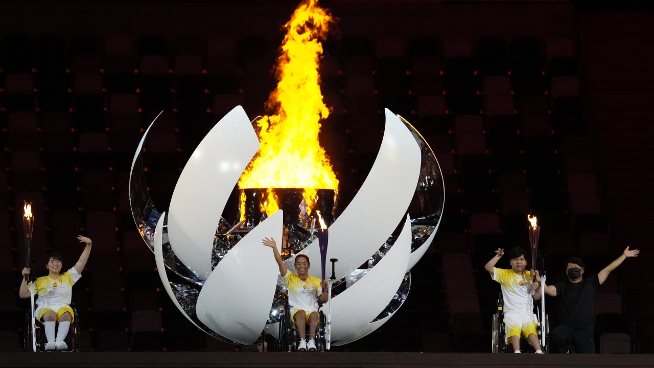 Japanese athletes wave after lighting the Paralympic cauldron.