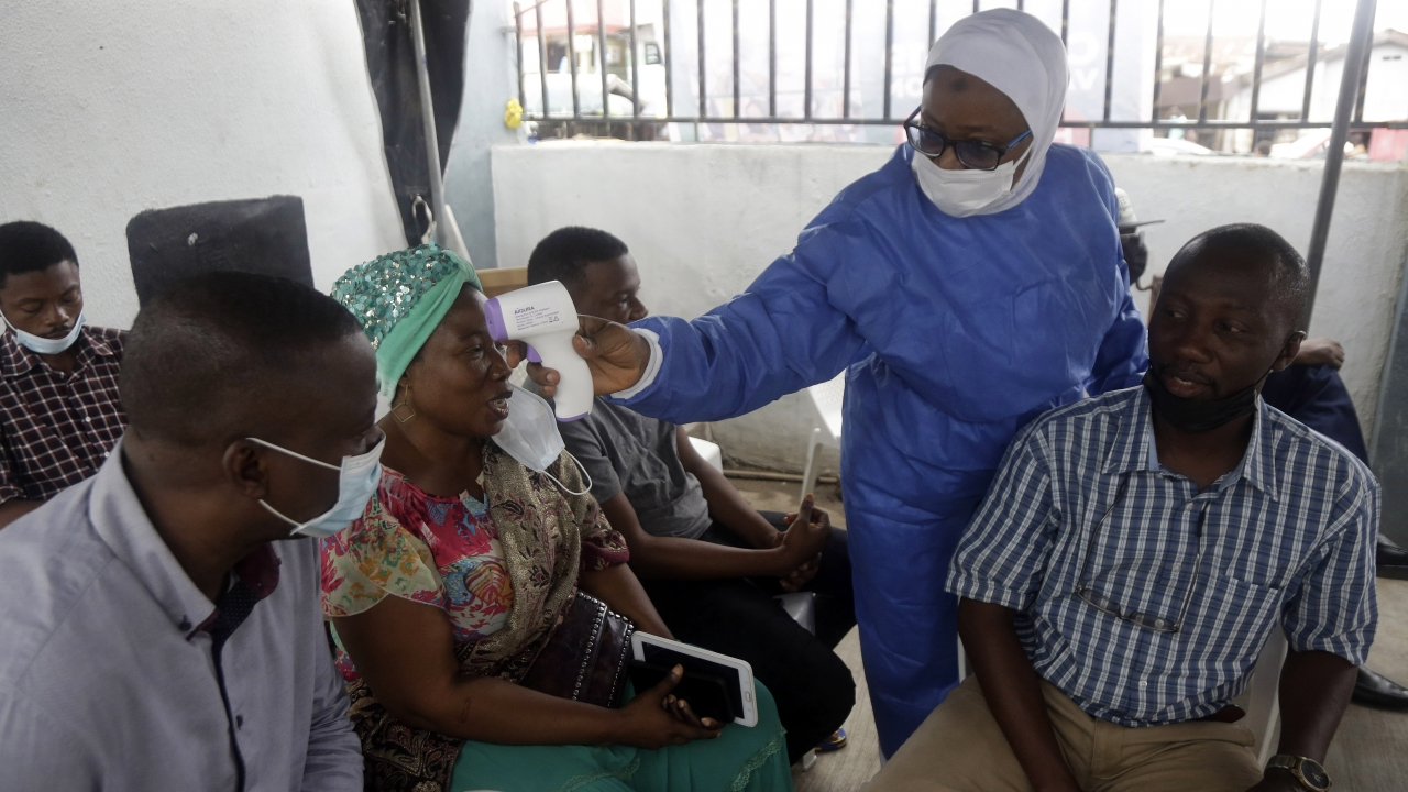 A nurse in protective gear, center, takes temperature of people waiting to take the Moderna coronavirus vaccine