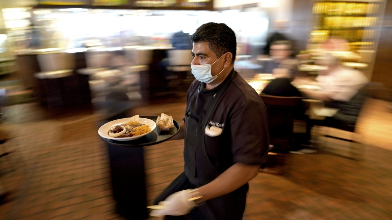 Marcelino Flores wears a face mask as he delivers food to a table at Picos restaurant in Houston in March 2021.