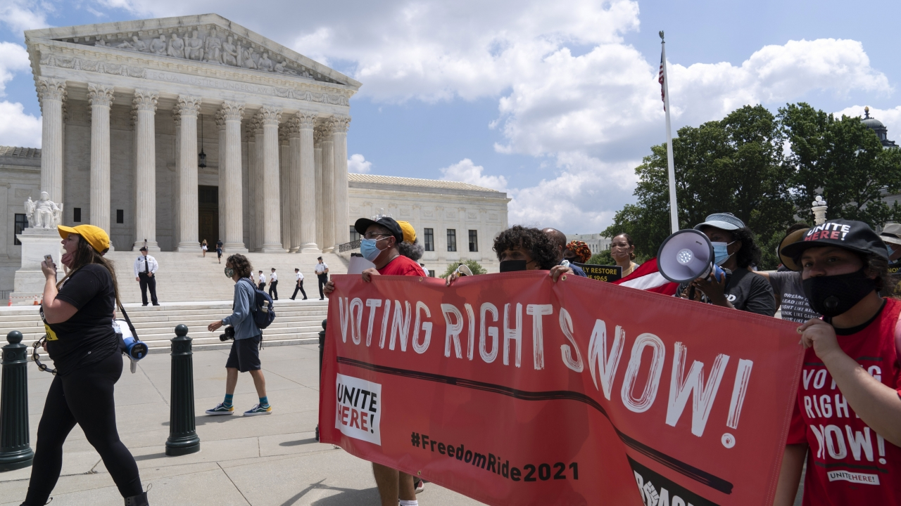 Voting rights activists march outside of the U.S. Supreme Court