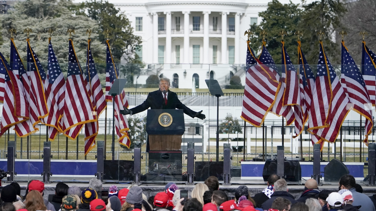 President Donald Trump speaks at a rally in Washington with the White House in the background.