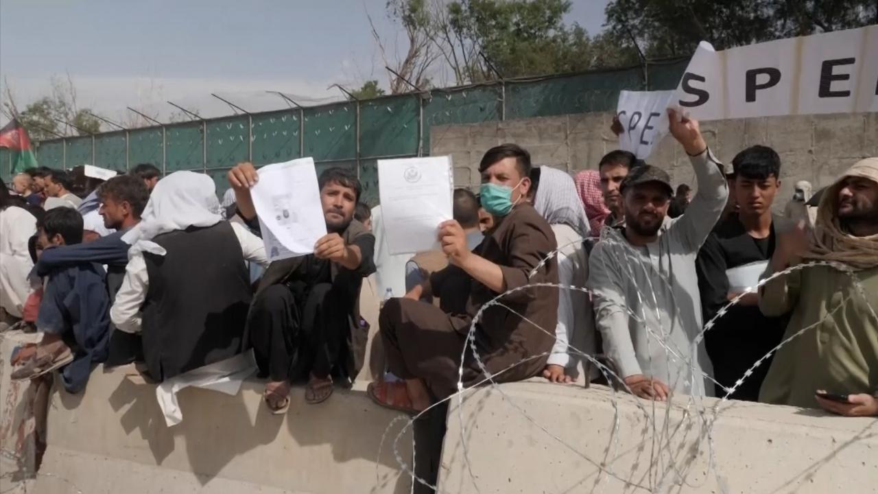 People wait to board evacuation flights in Kabul, Afghanistan