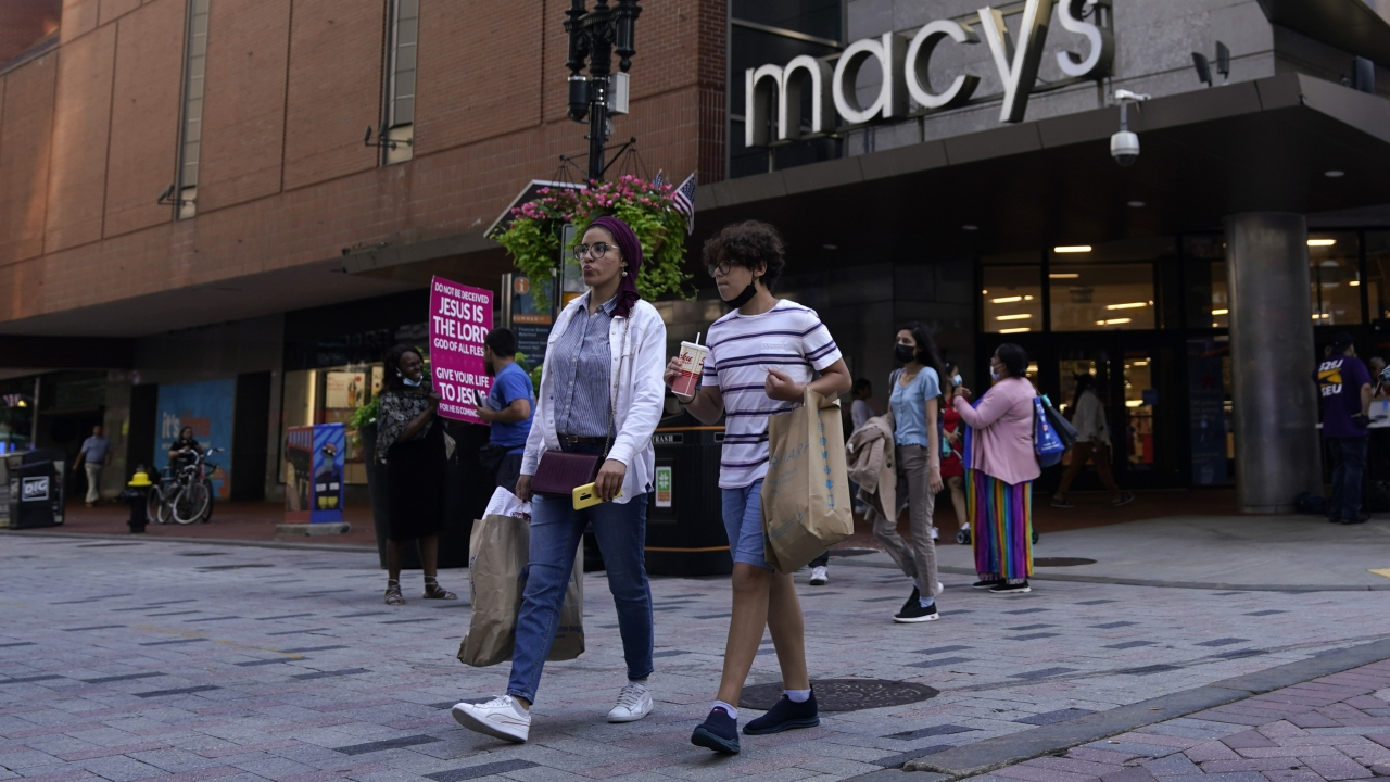 Pedestrians pass a Macy's store.
