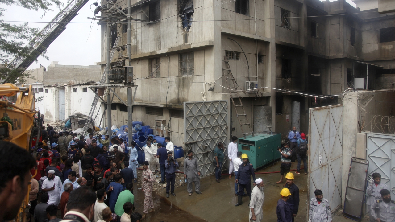Rescue workers search bodies at the site of a burnt chemical factory, in Karachi, Pakistan