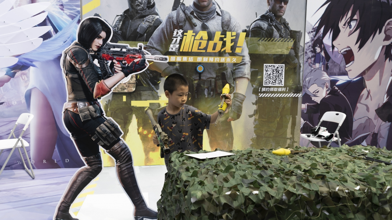 A child plays with a toy gun during a promotion for online video games in Beijing, China.