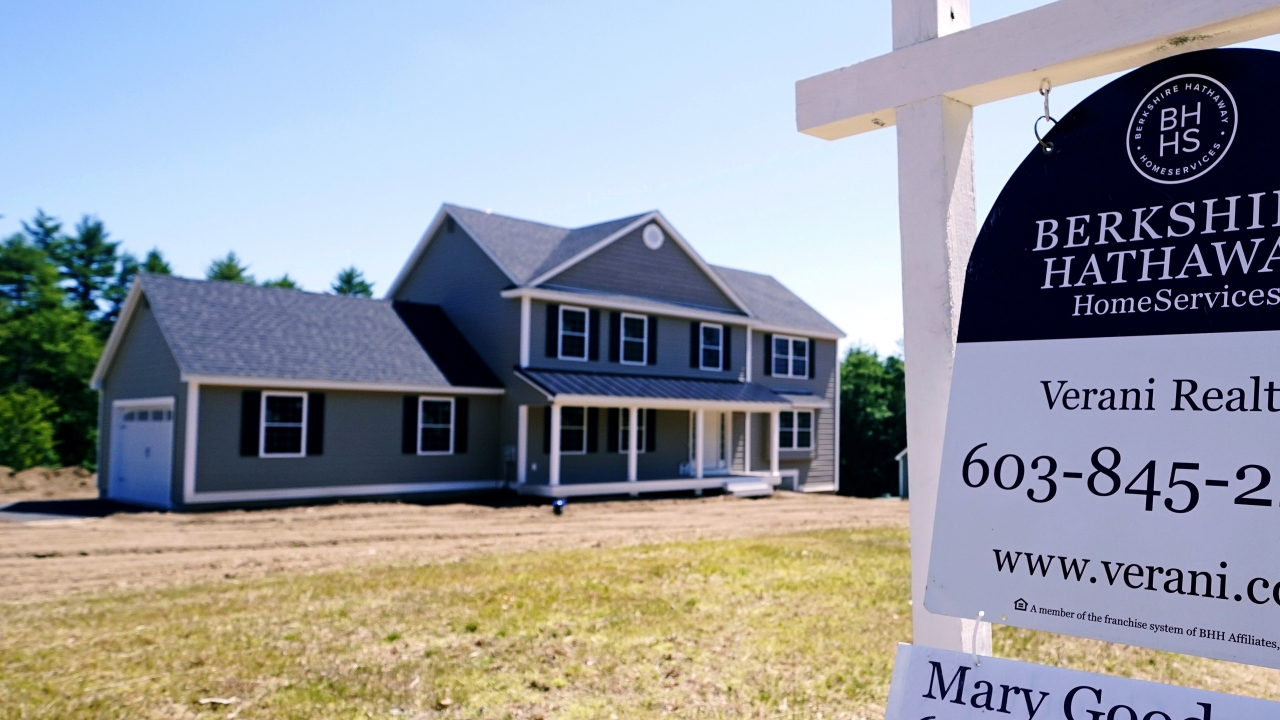A real estate sign is posted in front of a newly constructed single family home.