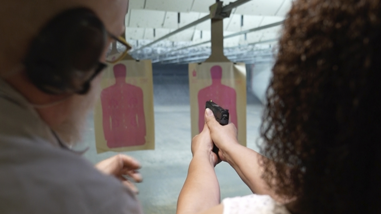 Valerie Rupert is instructed on the proper way of using a fire arm at the Recoil Firearms store in Taylor, Mich