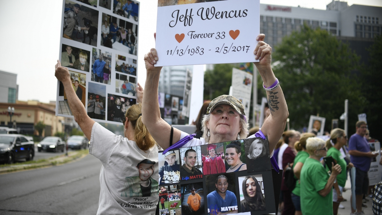 A woman holds a sign with a picture of her son and wears a sign of others' loved ones lost to OxyContin and other opioids.