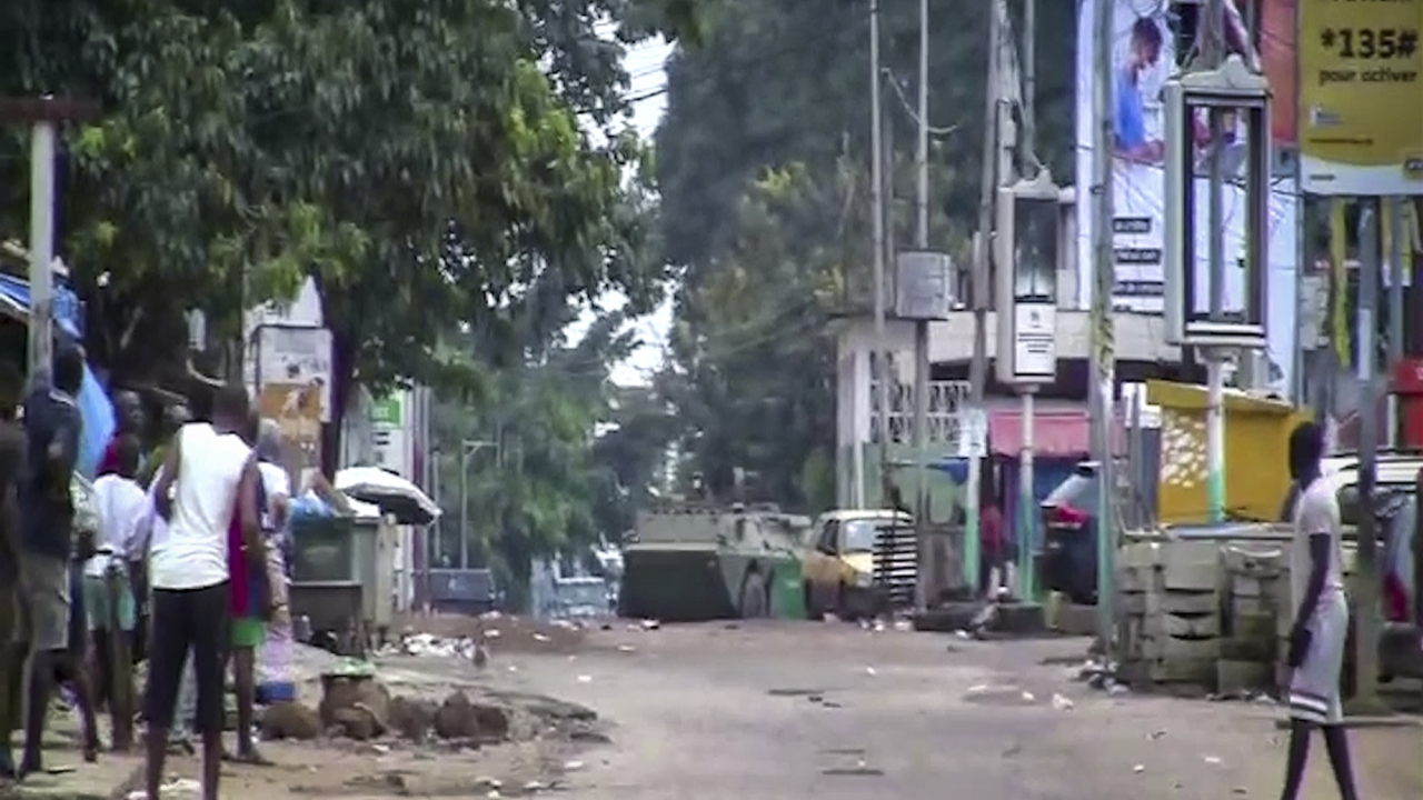 People watch as an armored personnel carrier is seen on the streets near the presidential palace in Guinea's capital.