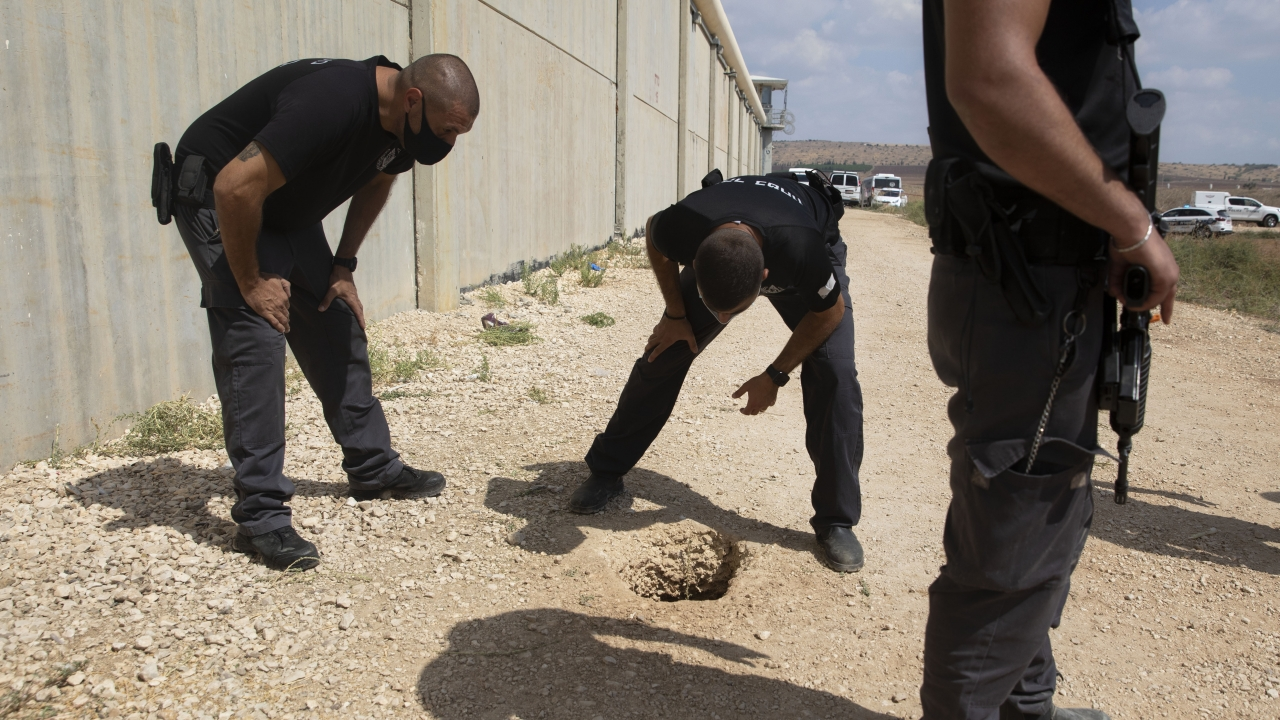 Police officers and prison guards inspect the scene of a prison escape outside the Gilboa prison in northern Israel.