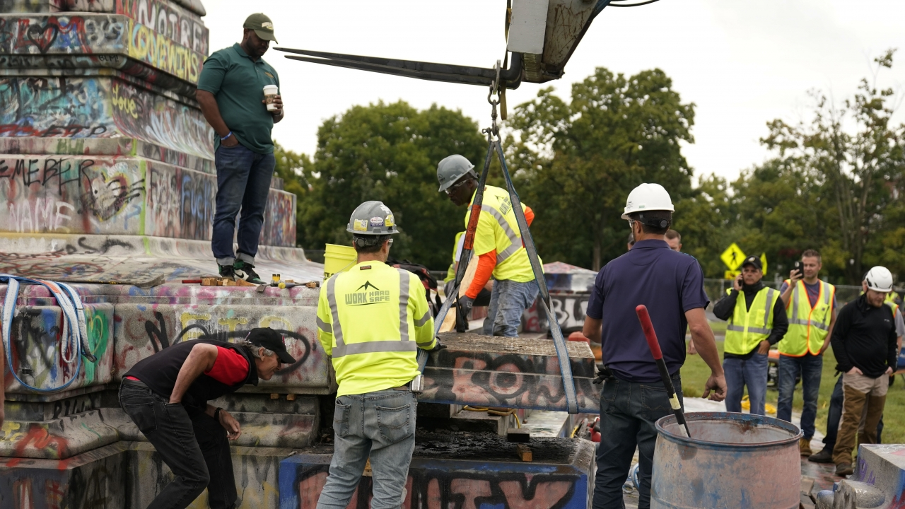Crews move a section of the base as they attempt to locate a time capsule said to be buried in the base of the statue.