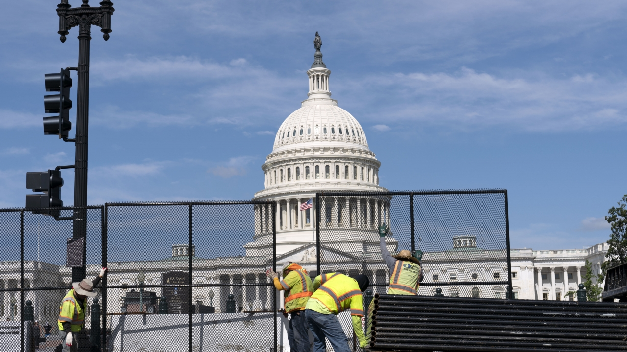 Workers remove the fence surrounding the U.S. Capitol building six months after it was erected.