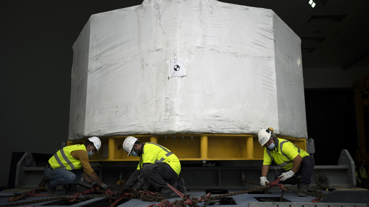 Workers receive a central solinoid magnet for the ITER project
