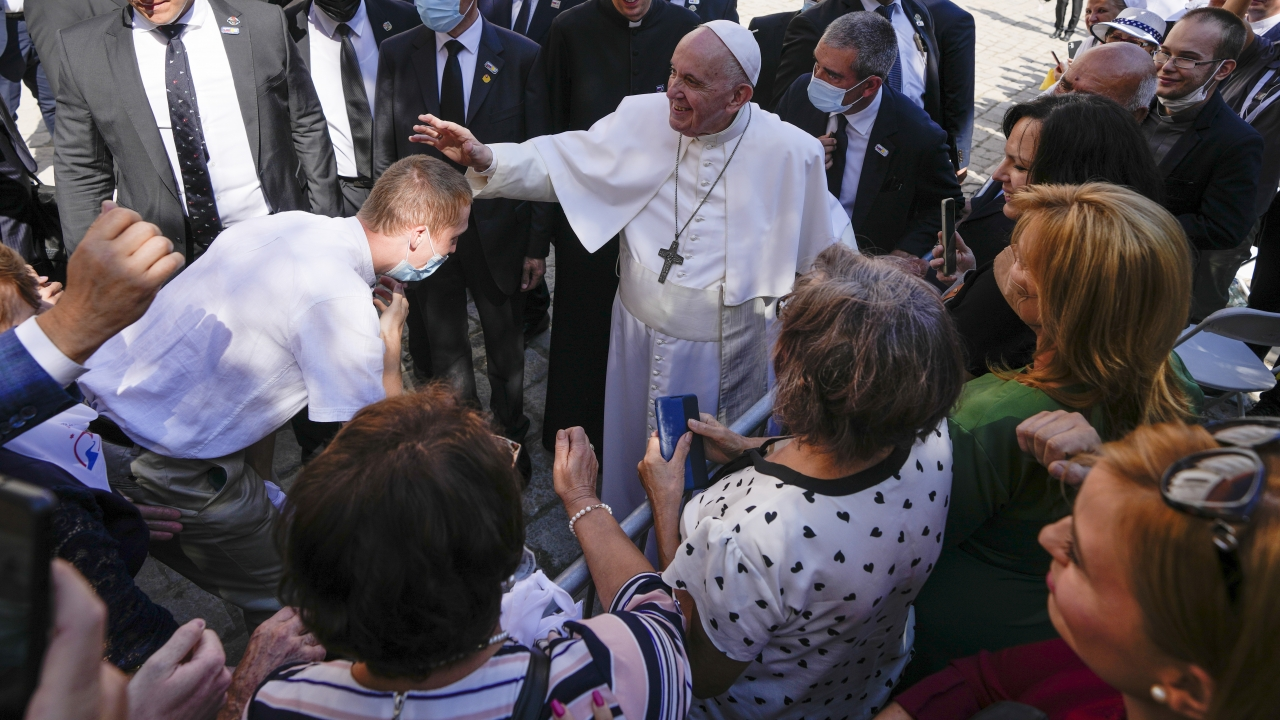 Pope Francis blesses an unidentified man as he greets the crowd while leaving the Cathedral of Saint Martin,