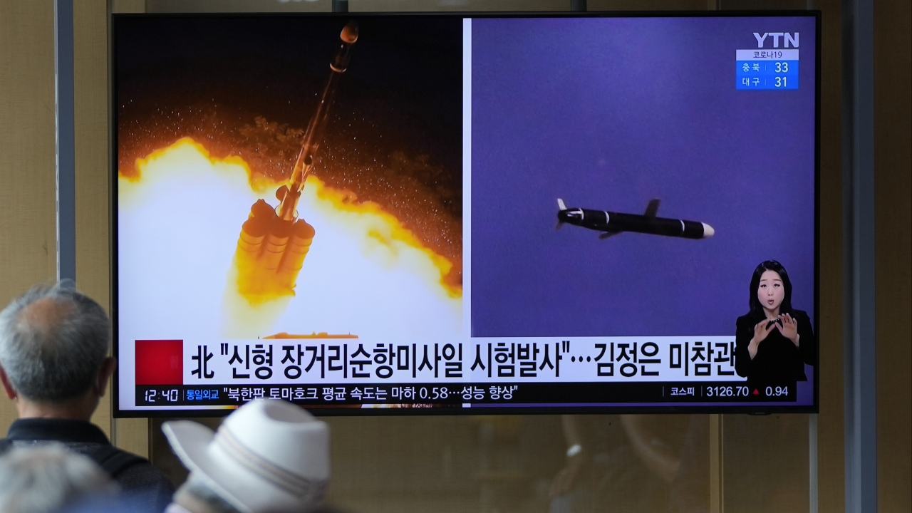 People watch a TV screen showing a news program reporting about North Korea's long-range cruise missiles