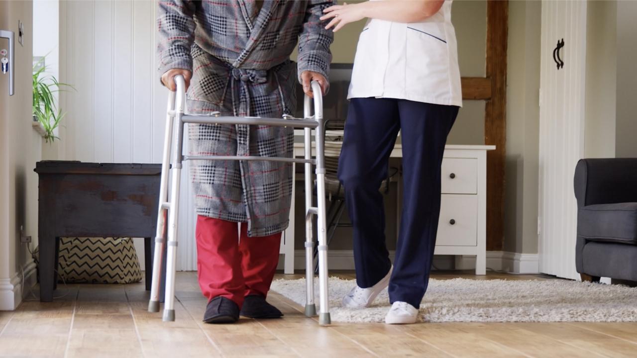 Nursing home staff member helps elderly patient