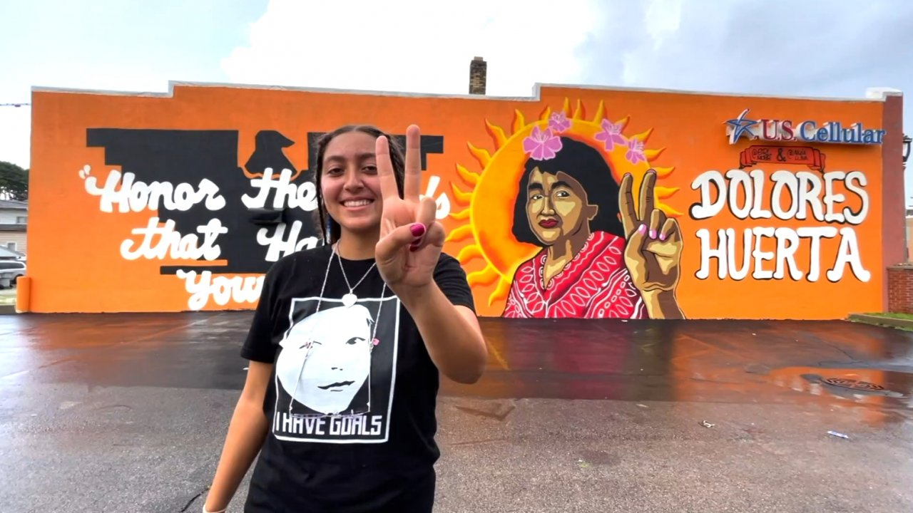 Woman stands in front of a mural.