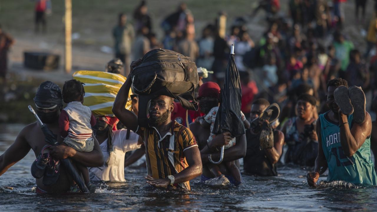Migrants, many from Haiti, wade across the Rio Grande river from Del Rio, Texas, to return to Ciudad Acuña, Mexico