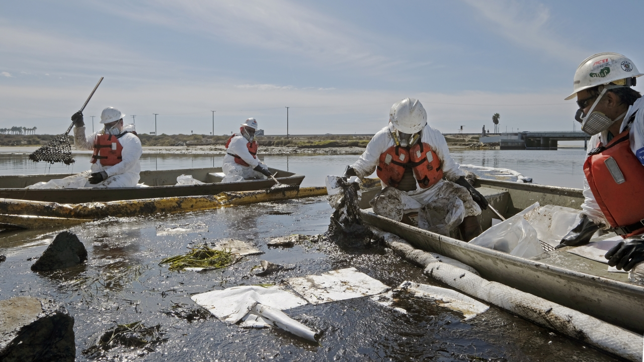 Workers in boats clean up oil in water.