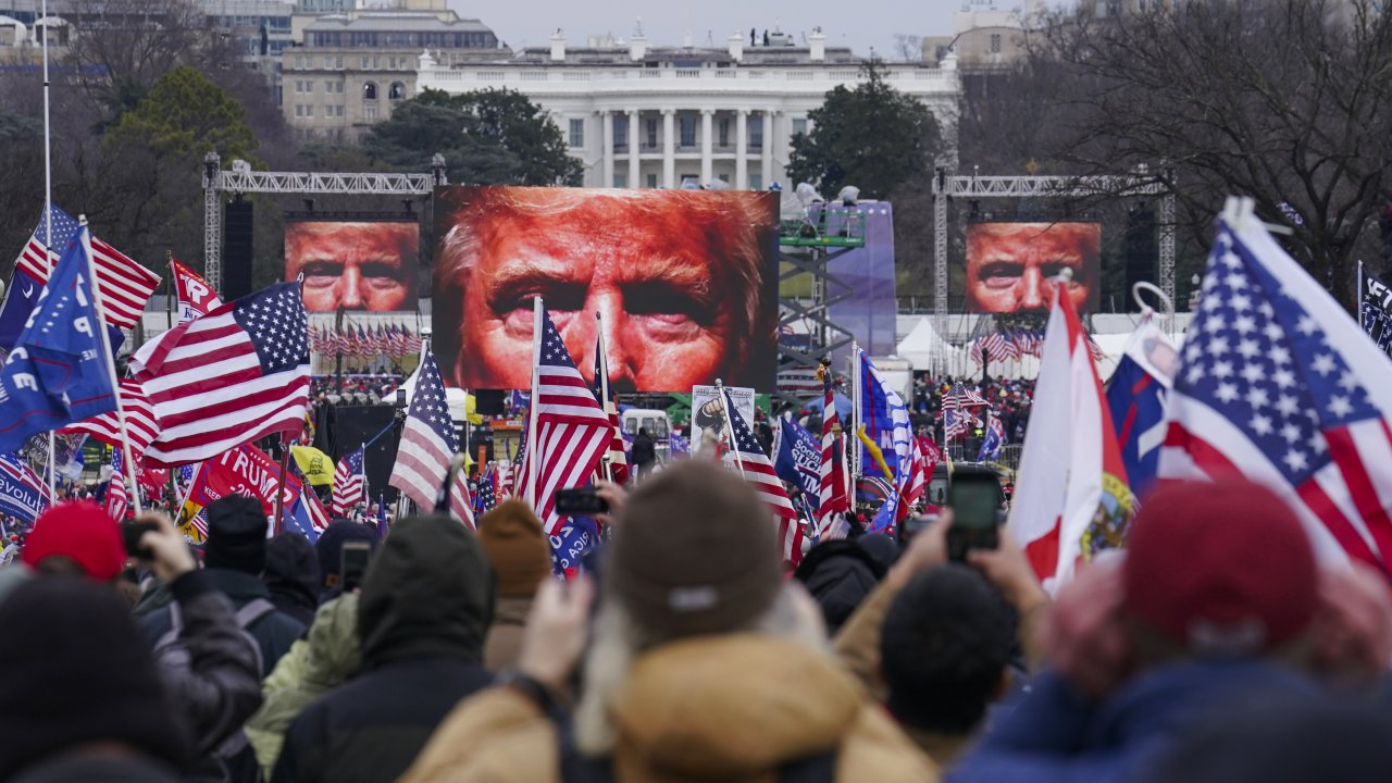 the face of President Donald Trump appears on large screens as supporters participate in a rally in Washington.