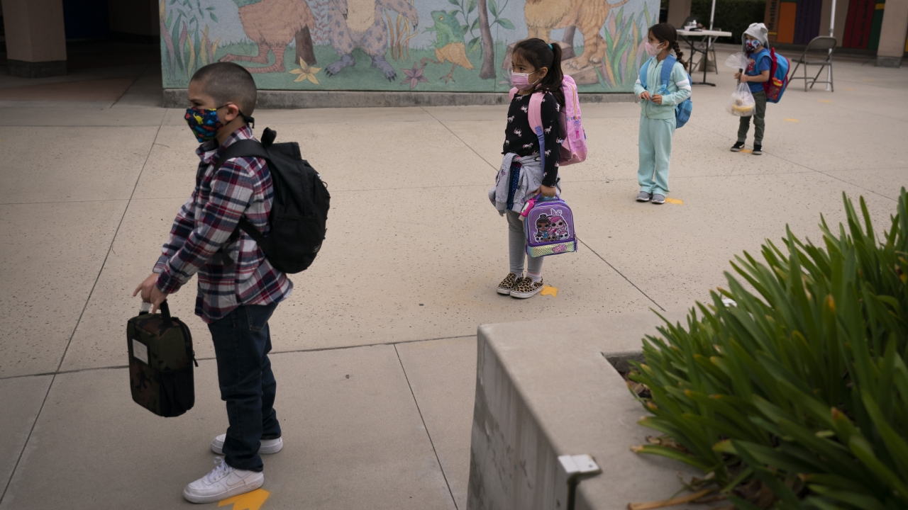 Socially distanced kindergarten students wait for their parents to pick them up.